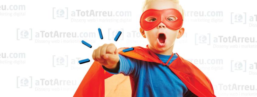 Un nen disfressat de superheroi en posició de lluita sobre uns logos d'atotarreu.com